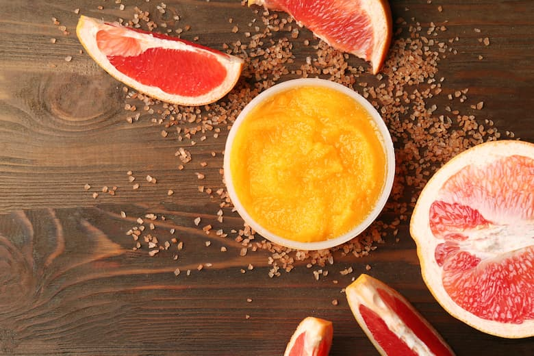 body scrub and grapefruit on wooden background